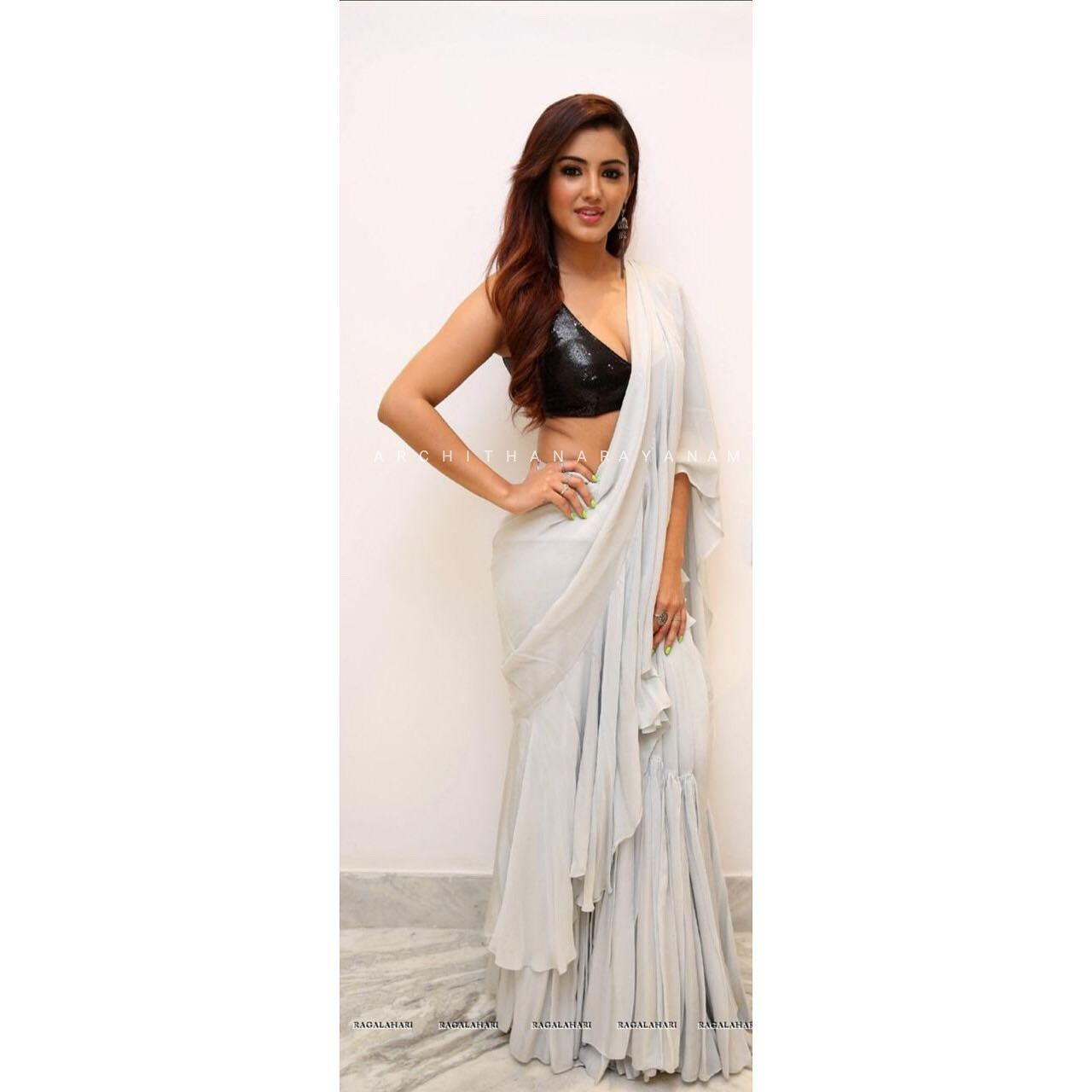 A pastel grey classic chiffon ruffled saree paired with a black sequence blouse will be classy evening affair!