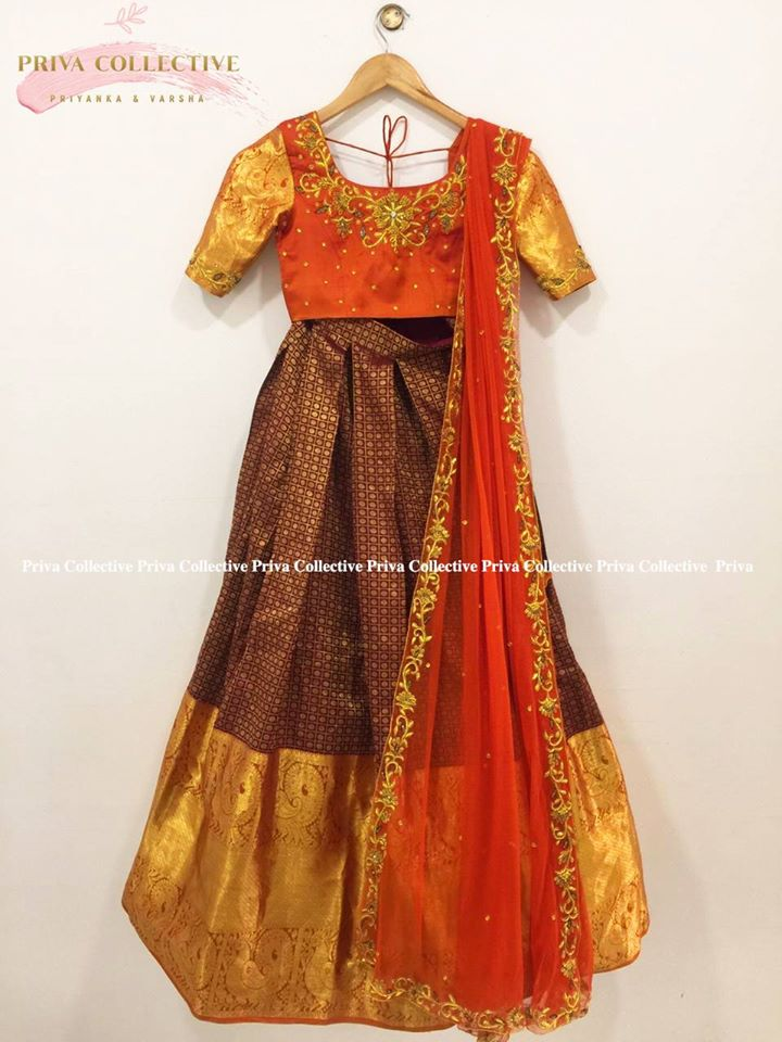 Stunning brown color kanchi pattu lehenga and orange color blouse with net dupatta. Blouse with zari sleeves.