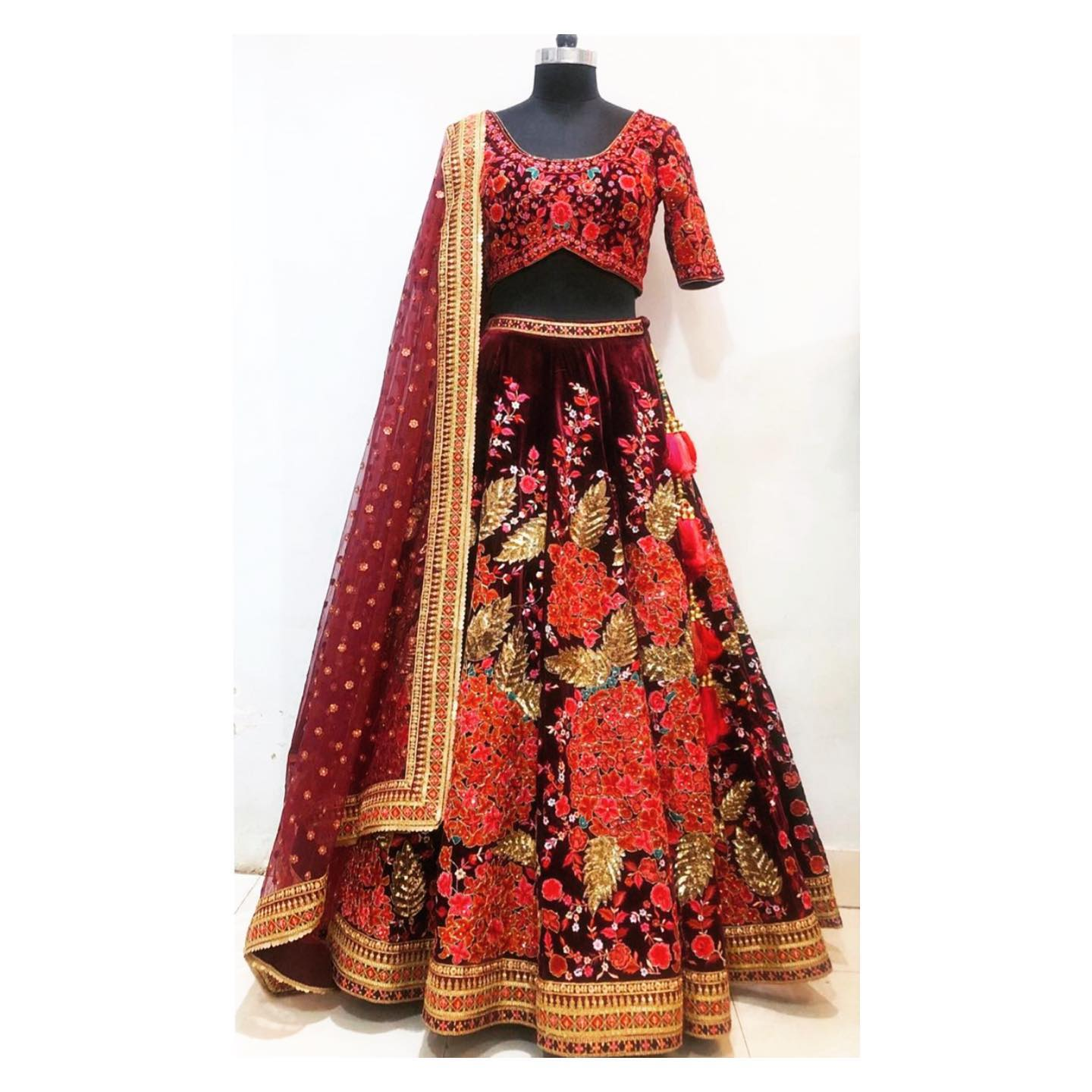 Hand embroidered bridal lehenga in deep maroon velvet.