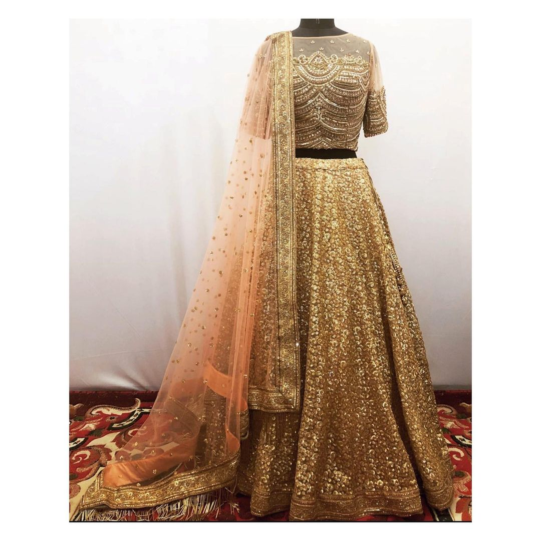 Gold and peach lehenga with sequins zardozi and kundan embroidery. Can be customised in any color or size. To order/customize/enquiry  email at shivani@intricado.com or  Whatsapp at +918527463626. | lehenga saree price | plain lehenga | best lehenga choli | 2020-11-27