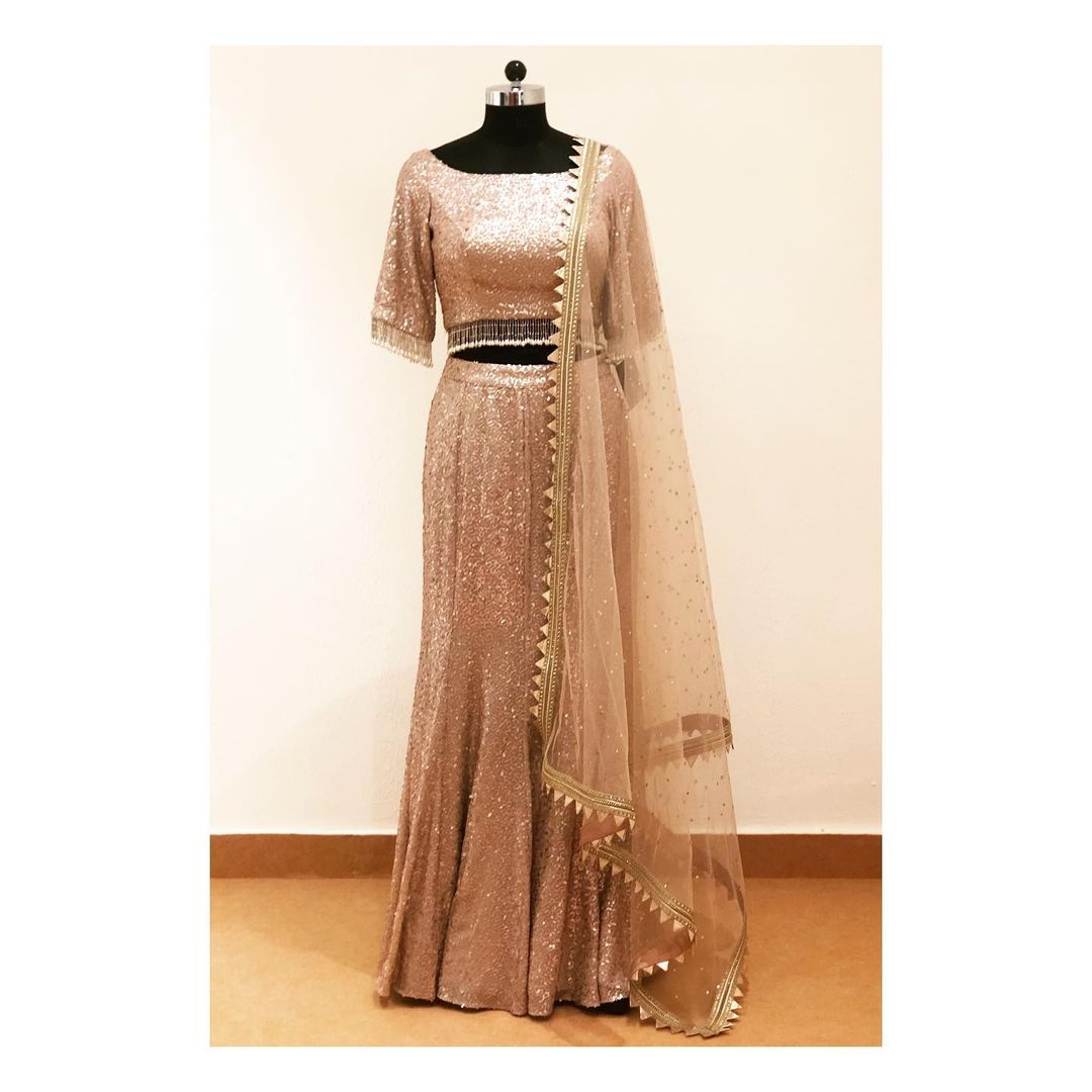 Champagne coloured Sequins work fish cut lehenga with pearls & beads detailings on blouse.