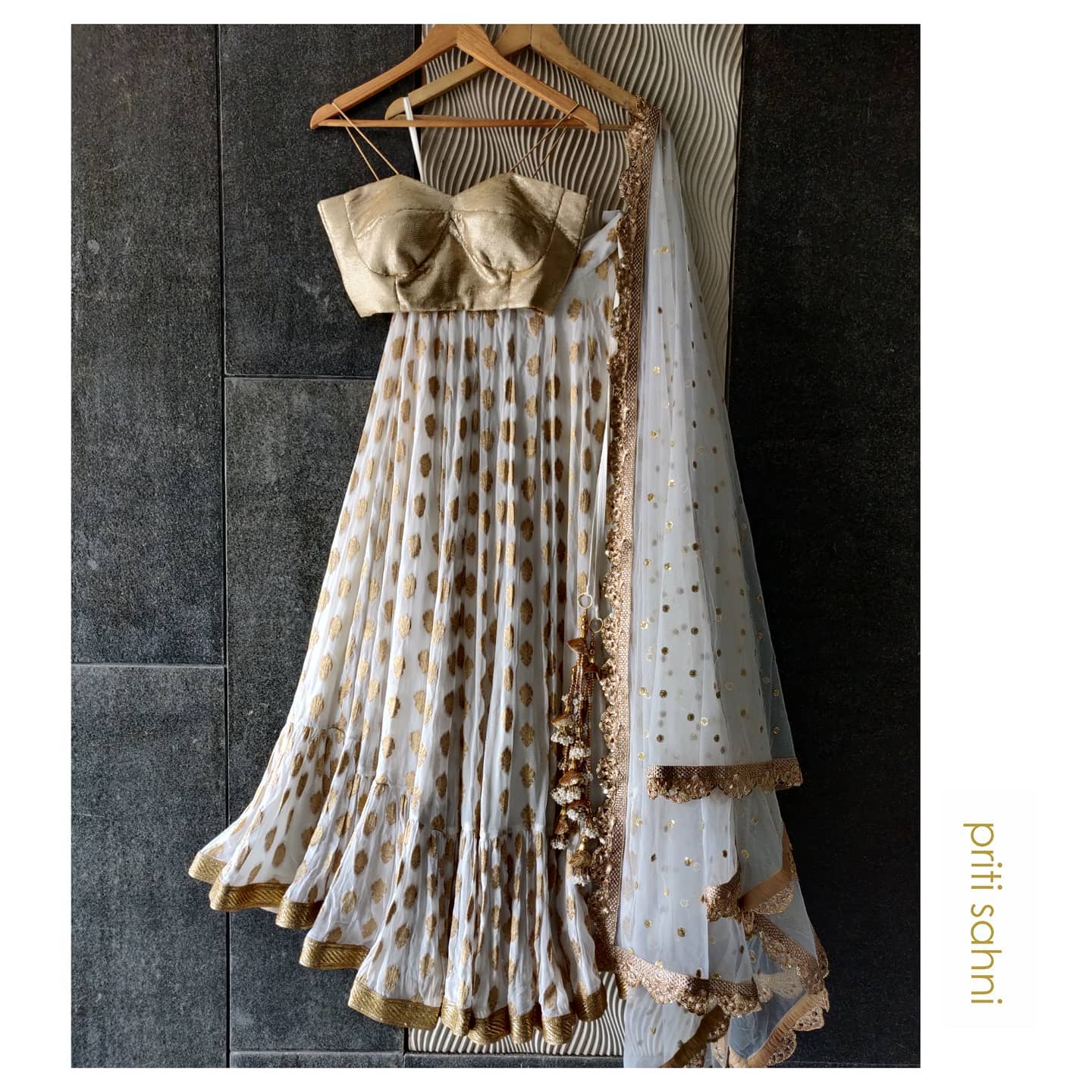 Ivory Edit  Ivory butti georgette lehenga with big ruffle detailing paired with champagne gold sequinned bustier and peach dupatta  To get your dream outfit designed  Whatsapp on +91-9022617481. | a line lehenga | lehenga with price  | lehenga designs 2020 | 2020-12-05