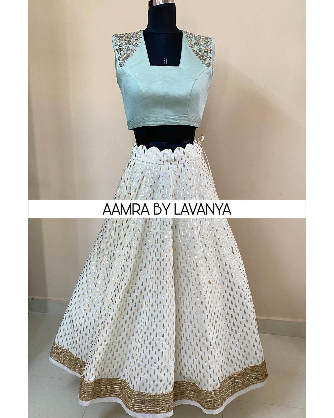 Halfwhite lehenga paired with an intricately hand embroidered iceblue glass neck croptop blouse.