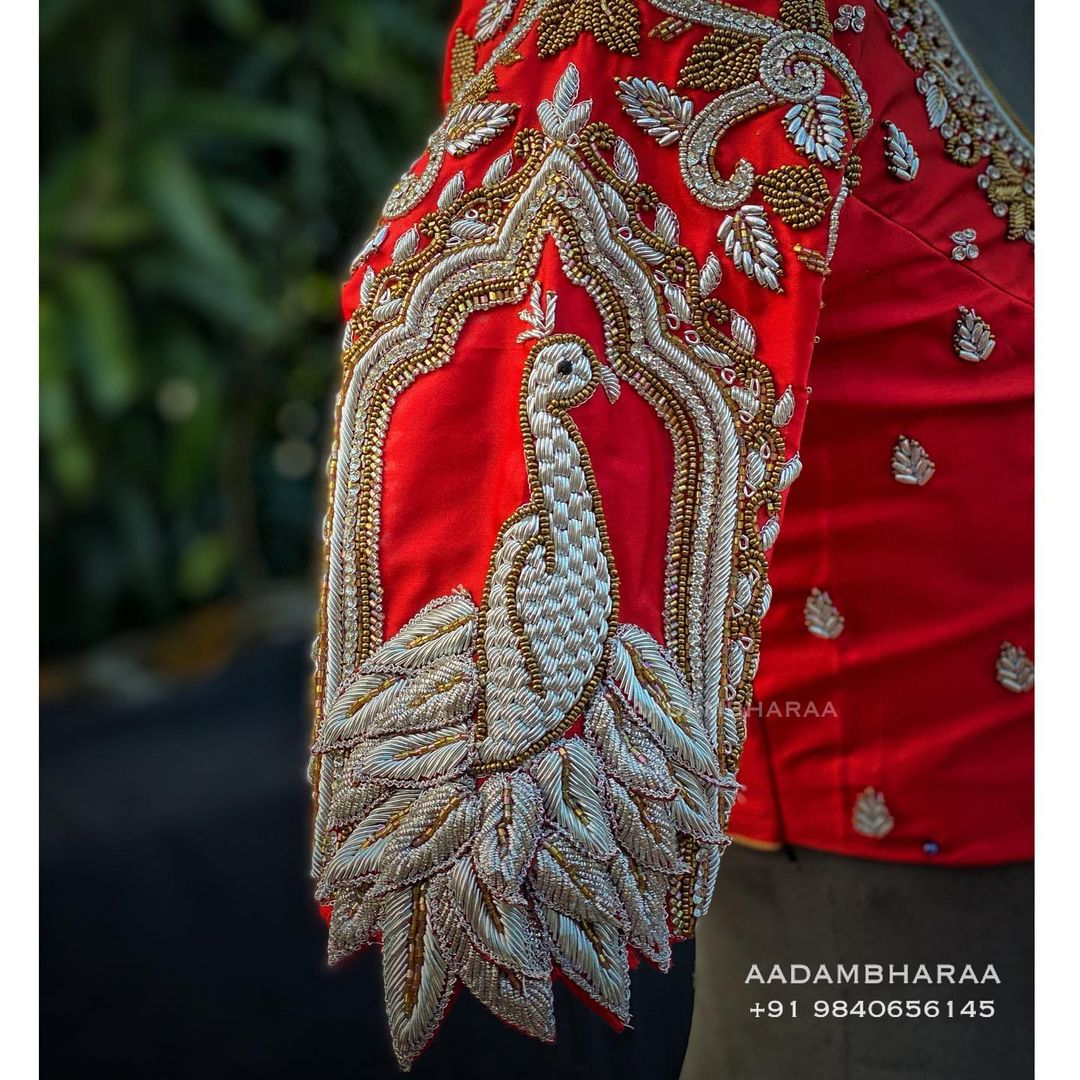 Add a new dimension to your wardrobe with Aadambharaa's unique 3D motif blouse. The beautiful red blouse is decked with hand embroidered peacock design whose zardosi feathers add an interesting twist to your traditional ensemble! | plain blouse designs | blouse ke design blouse ke design | blue blouse design | 2020-12-24