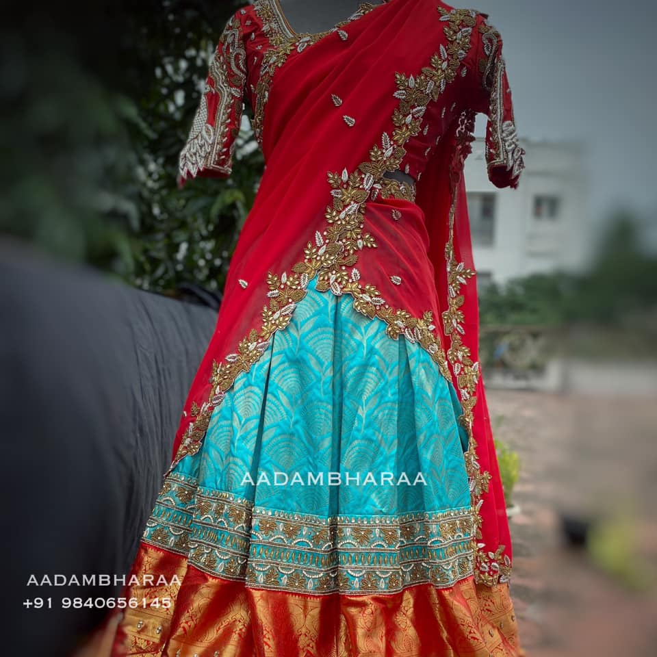Here is a stunning and fuss free look for your reception from Aadambharaa for your wedding trousseau. The blue Pure silk lehenga skirt and the red georgette cut work dupatta paired with heavy 3D Peacock blouse is sure to wow the guests and create a timeless look on your big day!