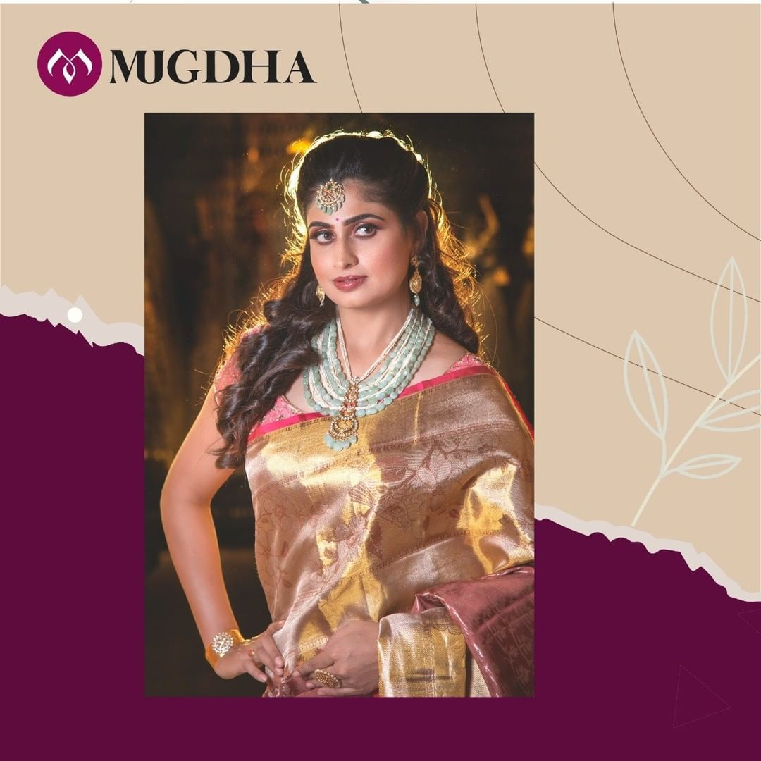 Beautiful Red-Orange shade Kanjeevaram Saree with a perfect zari work is an absolute pick for your special day. The grandeur of Gold emphasizes the look even more.  Wear with style and grace the new collection of Mugdha. 2021-01-08