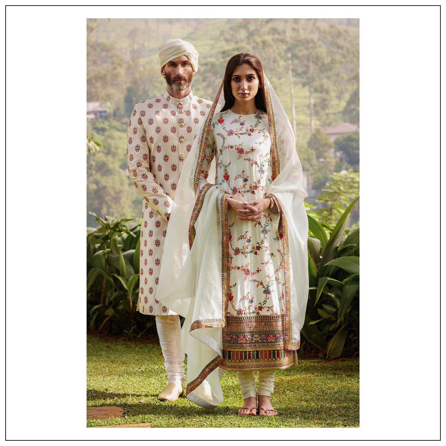 The lady is wearing a khadi kurta meticulously embroidered with Kashmiri thread work. It is detailed with embroidered borders and paired with a crisp white khadi churidar and an embroidered organza dupatta.  The gentleman wears a silk sherwani meticulously embroidered with Kashmiri thread work and accessorised with hand crafted gold plated Bengal tiger buttons and a silk kota safa. 2021-01-16