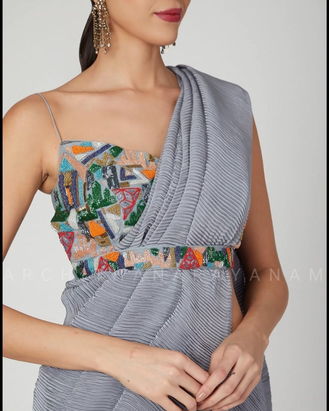 A classy compressed draped chiffon saree worn with a charming stylised blouse embroidered in multi colour bead work abstract style. An ecstatic contemporary style apt for a party wear. 2021-01-24
