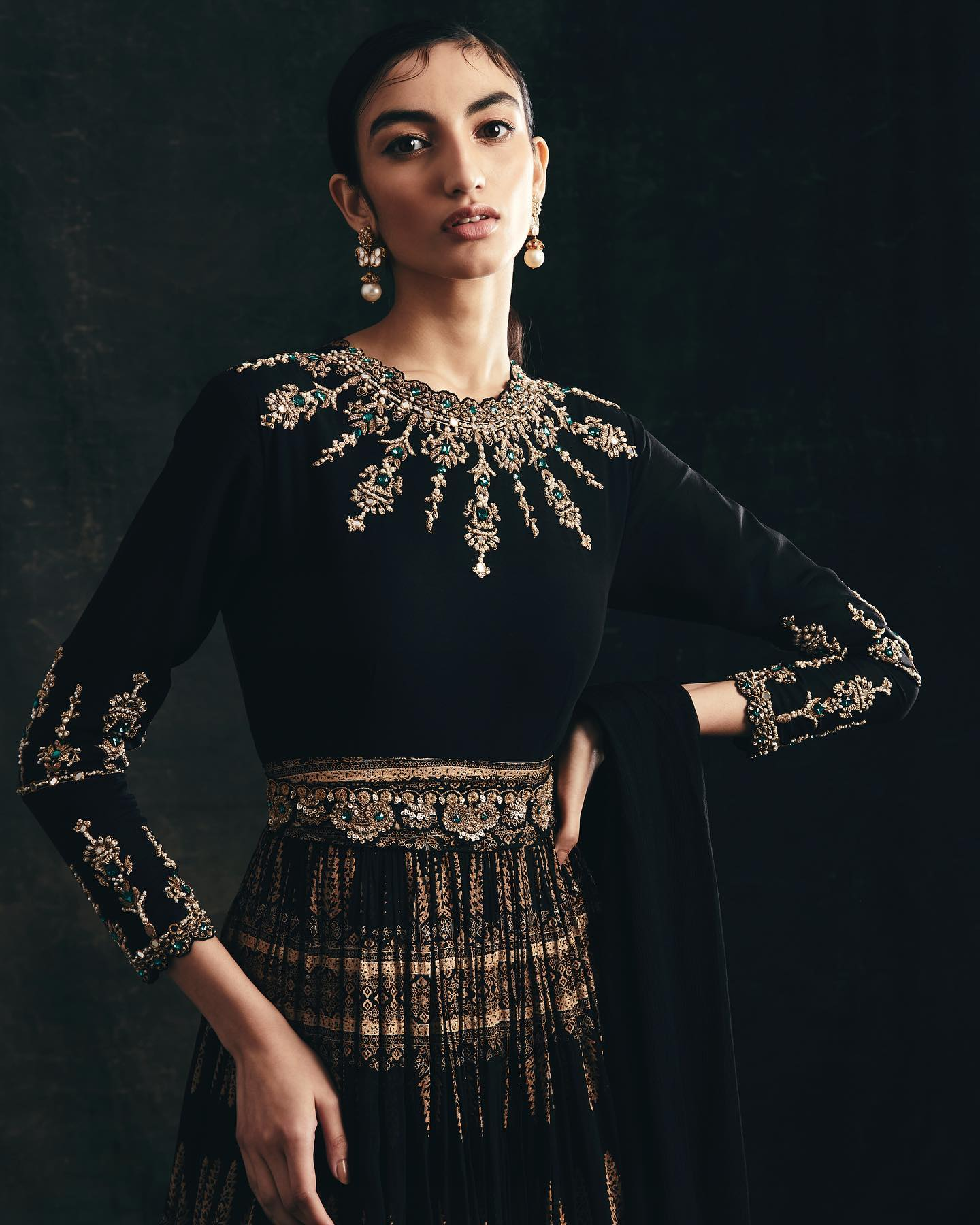 THE MIDNIGHT SUN . FESTIVE 2021.  LOOK 5 - Black anarkali with gold persian print pleated ghera. The yoke and sleeves are embroidered with tilla  pearl  dabka and emerald green stones. The look is finished with fabric and embroidered belts and solid black dupatta. 2021-02-09
