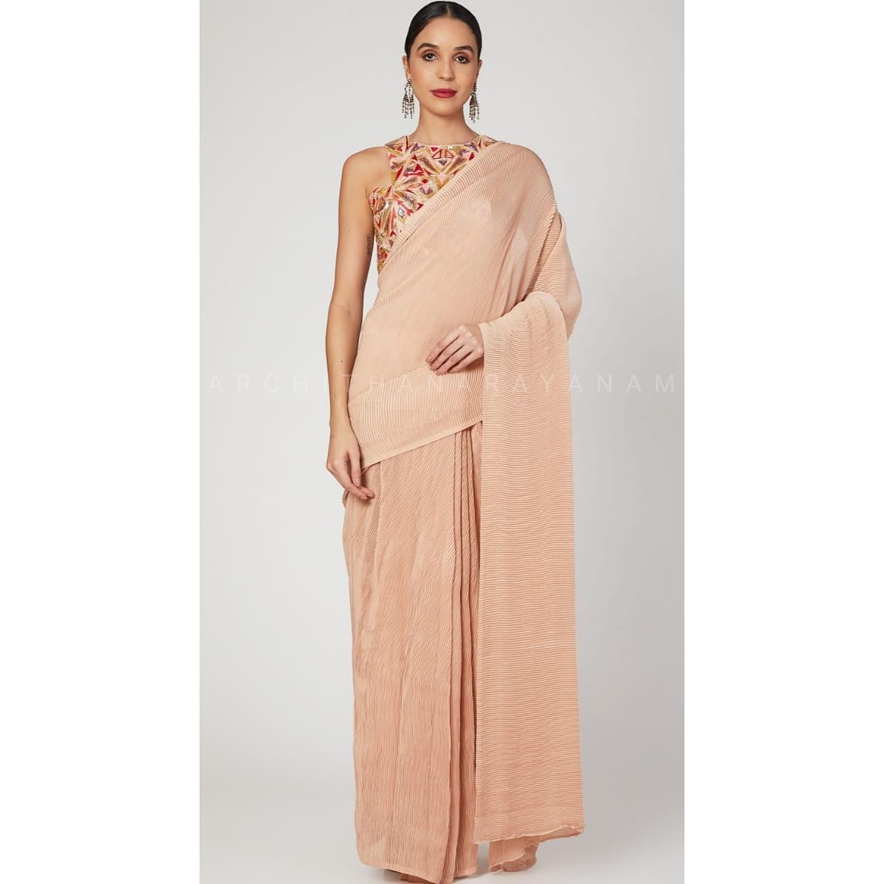 A classy compressed draped chiffon saree stylised with an off shoulder blouse embroidered in warm hues of crimson peach burgundy and gold. Looking ecstatic in this contemporary party wear. 2021-02-18
