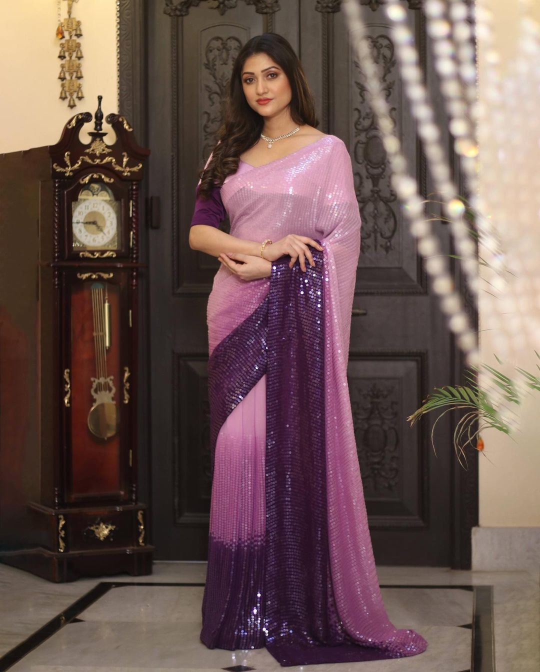 In an easy drape this georgette piece of designer wear is a perfect outfit for social gatherings. Shaded in pink and purple and composed with sequins embroidery all over this saree holds magnificent grace.