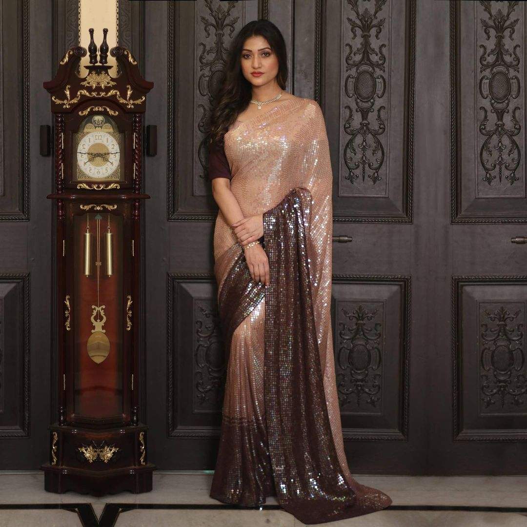 In an easy drape this georgette piece of designer wear is a perfect outfit for social gatherings. Shaded in beige and brown and composed with sequins embroidery all over this saree holds magnificent grace.