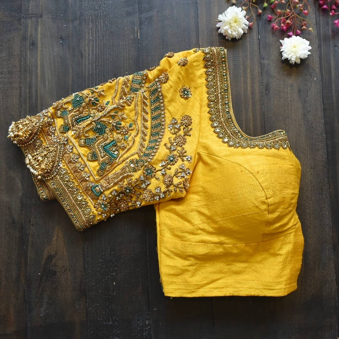 Love traditional elephant embroidery on your bridal blouse? This is one of SRUTHi KANNATH recent favourite and a so-in-lobe colour combination of this season. Stunning yellow color designer blouse with elephant embroidery maggam work. 