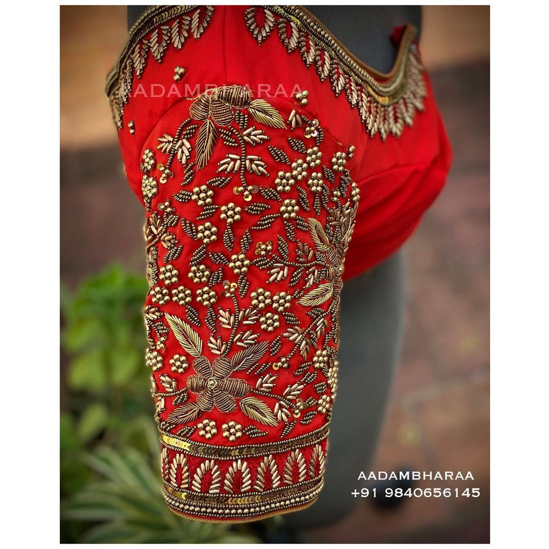 This red bridal blouse from Aadambharaa with hand embroidered golden flowers and Zardosi leaves and motifs is the perfect blend of elegance and extravagance .