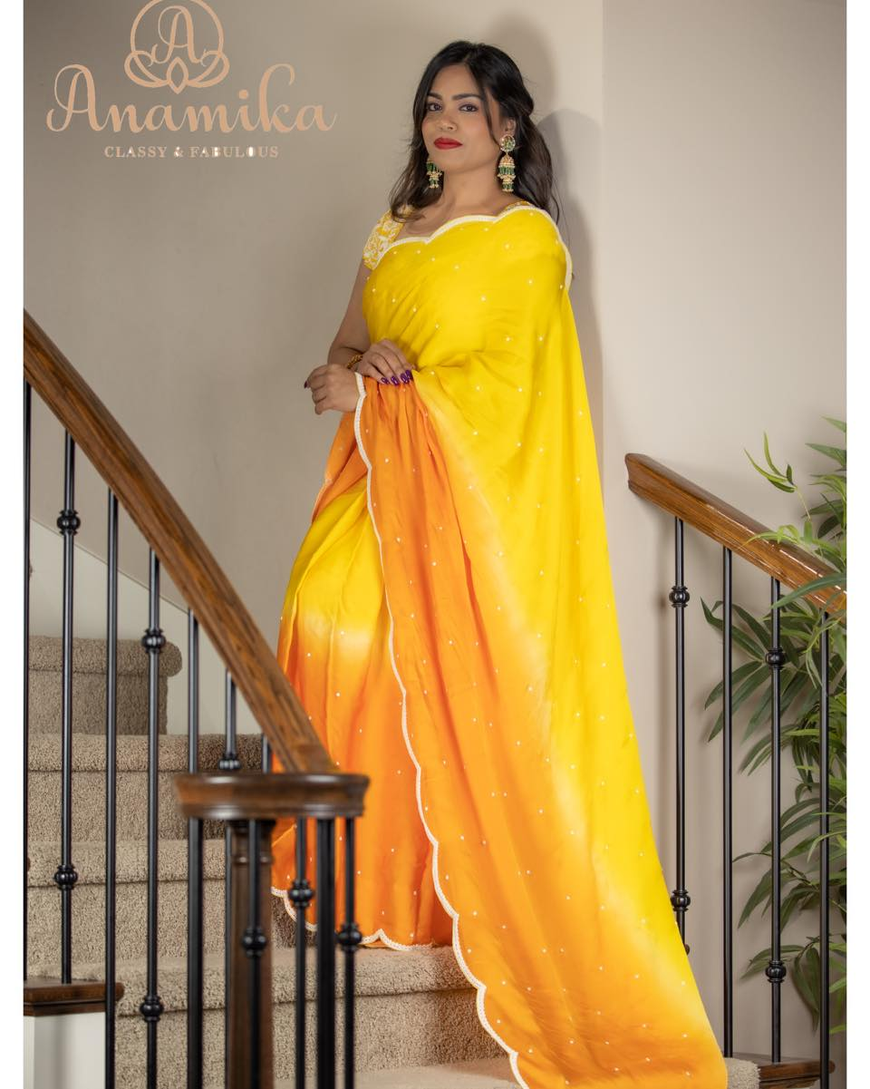 A stunner satin organza saree in the most appealing shades of yellow and orange – beautified with a pearl work border. The captivating pearl work blouse exemplifies the beauty of this saree. It sure is a visual treat for eyes 2021-02-26
