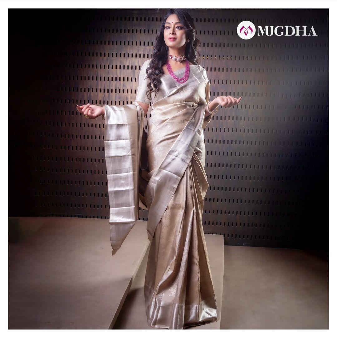 Luxurious Silver Kanjeevaram saree is intricately weaved with tree motifs all over the saree with Shiny silver threaded zari border and rich pallu with wonderful craftsmanship.  Rock this beauty on your special occasions and festivities.    For orders and enquiries: +91 7993710111. 2021-03-04