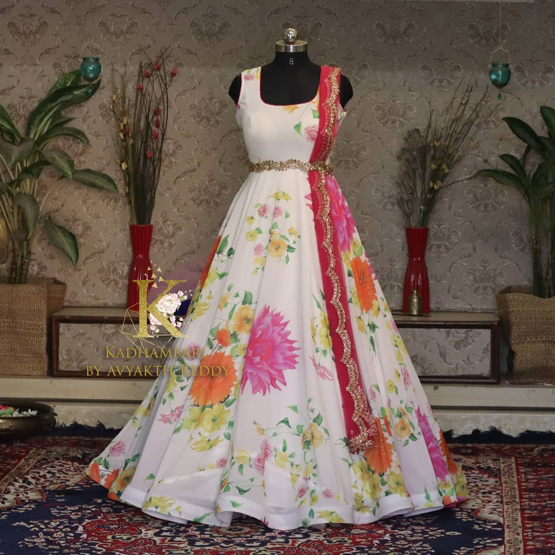 Stunning pearl white color floral print umbrella cut long frock with wasit belt and net dupatta.. This outfit is Available at Rs 6800/- from house of Kadhambari. THey can customize size as per your requirement. They have international shipping service too. For Orders and Enquiry Reach  on WhatsApp +91 8801876477 // +91 9063479099 2021-03-23