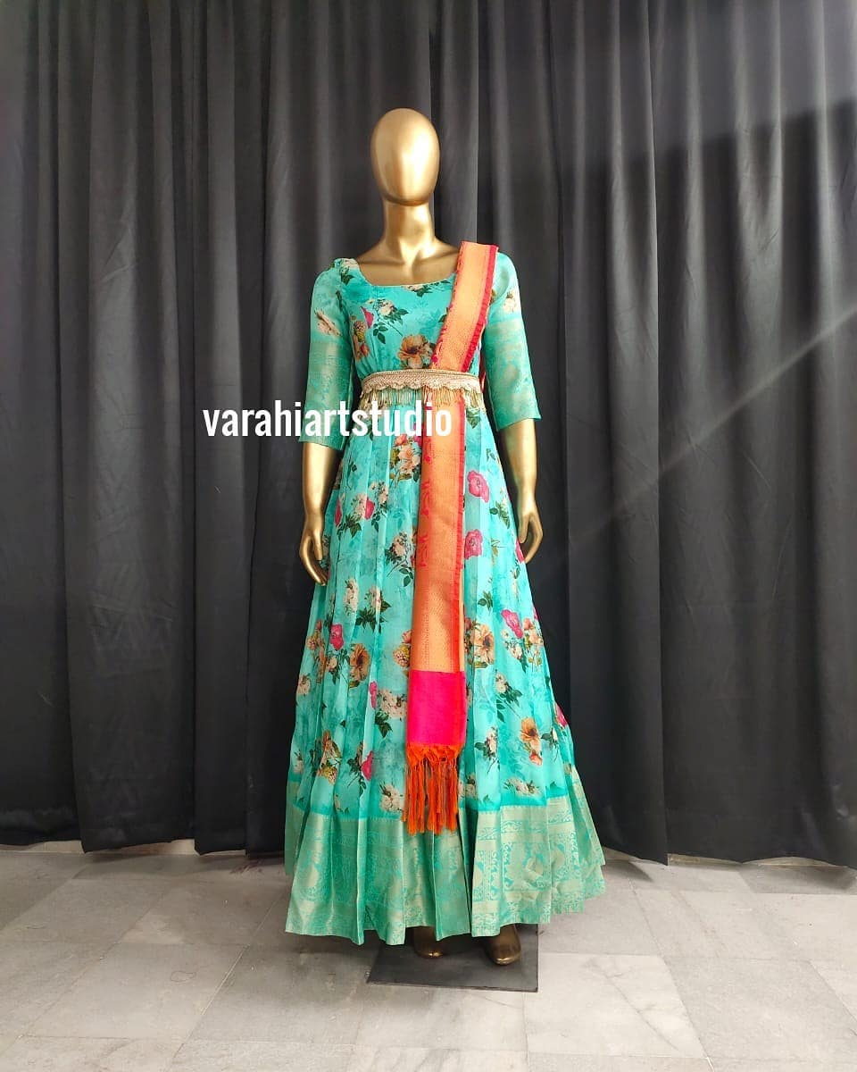 Gorgeous sea green color floral floor length pattu long frock with pattu dupatta. Pattu long frock with waist belt. This outfit is Available at Rs 6800 from Varahi art studio ..
