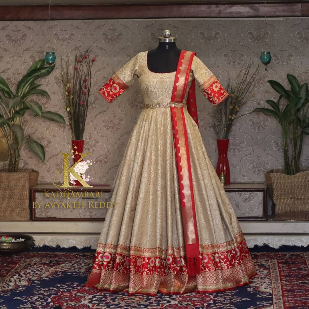 Stunning off white and red color combination traditional pattu long frock with pattu dupatta and wasit belt. This outfit is Available at Rs 6800/- from house of Kadhambari. They can customize size as per your requirement. They have international shipping service too. For Orders and Enquiry Reach  on WhatsApp +91 8801876477 //  +91 9063479099 2021-03-24