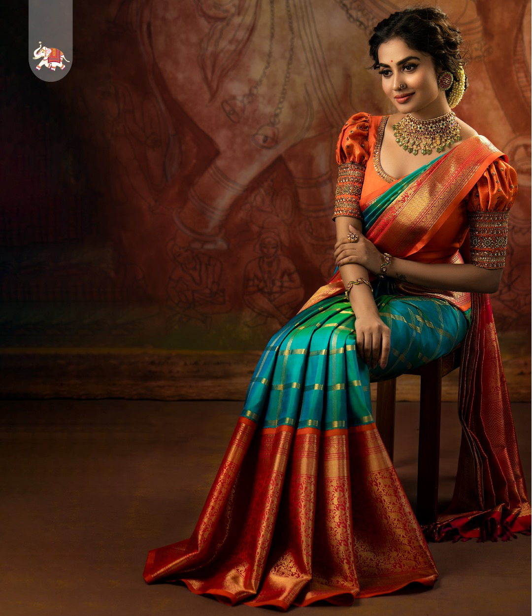 Classic bridal Kanchi korvai silk saree adorned with beautiful floral peacock horse and elephant motifs handwoven with golden zari on pink & orange border against turquoise blue checked kanchi silk. Elegance personified! 2021-03-28