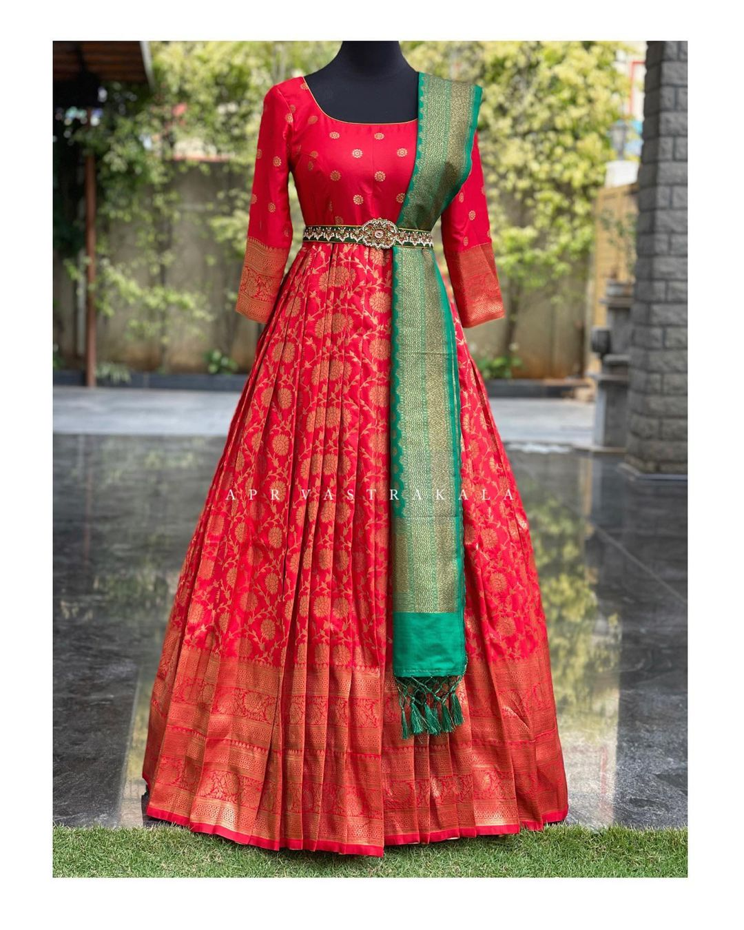 Stunning red color kanchi pattu long frock with green pattu dupatta and waist belt.