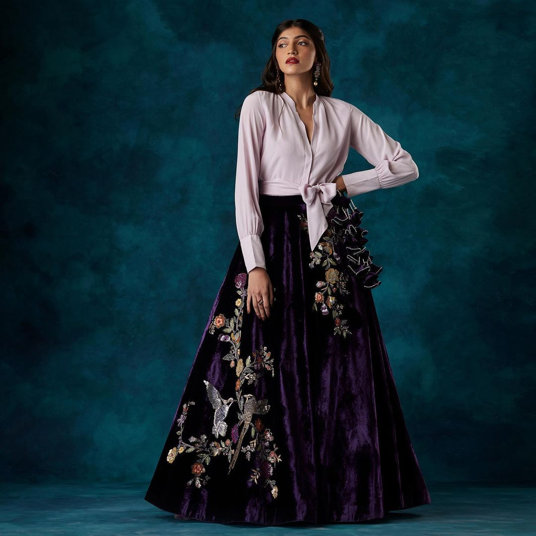 A modern skirt lehenga in eggplant velvet paired with a crepe silk tie-up shirt.