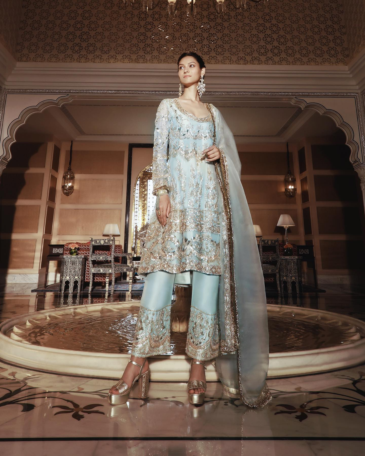 An incredible coalesce of traditional artistry with an elegant contemporary aesthetic in Manish Malhotra mint organza short Kalidar with delicate gold zardosi and sequins embroidery in a scalloped form and a tonal drape trimmed with gold Kinari! 2021-03-31