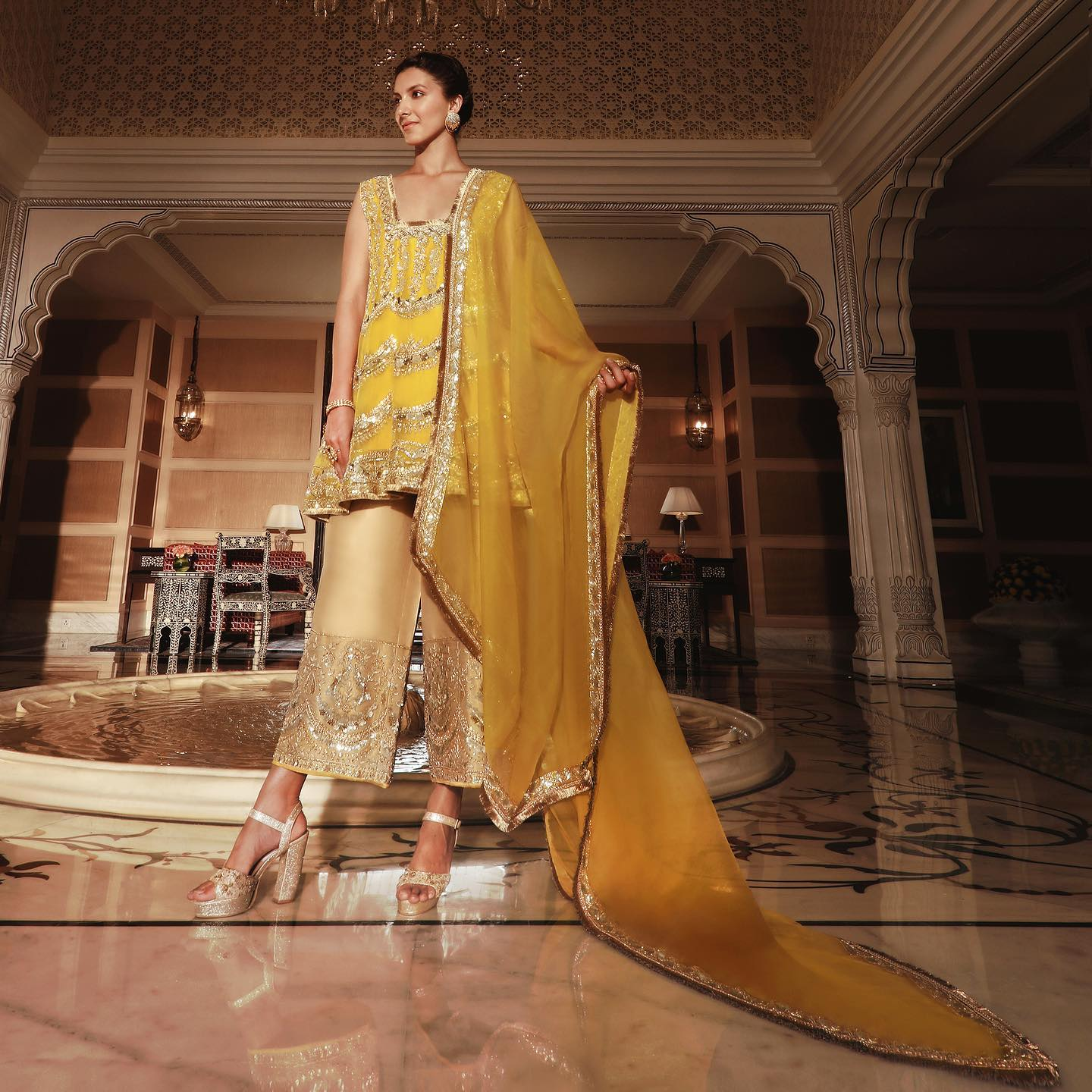 Featuring enamoured sequins and timeless zardosi Manish Malhotra sublime canary yellow ensemble paired with a scalloped organza drape and gold ankle-length palazzo is delicate regalia that beacons the illumination of a Tuscan sun! 2021-04-02