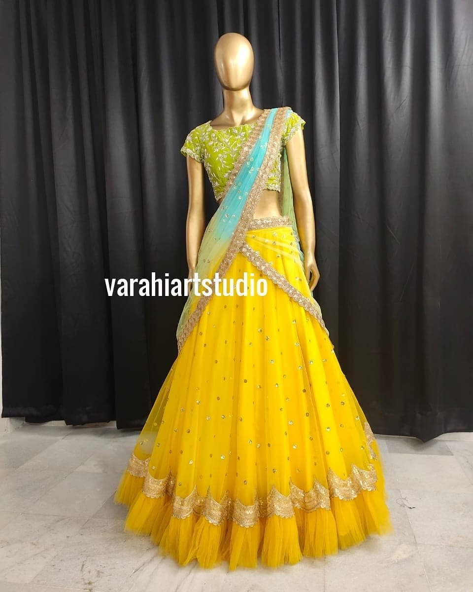 Stunning yellow color net lehenga and parrot green blouse with net dupatta.