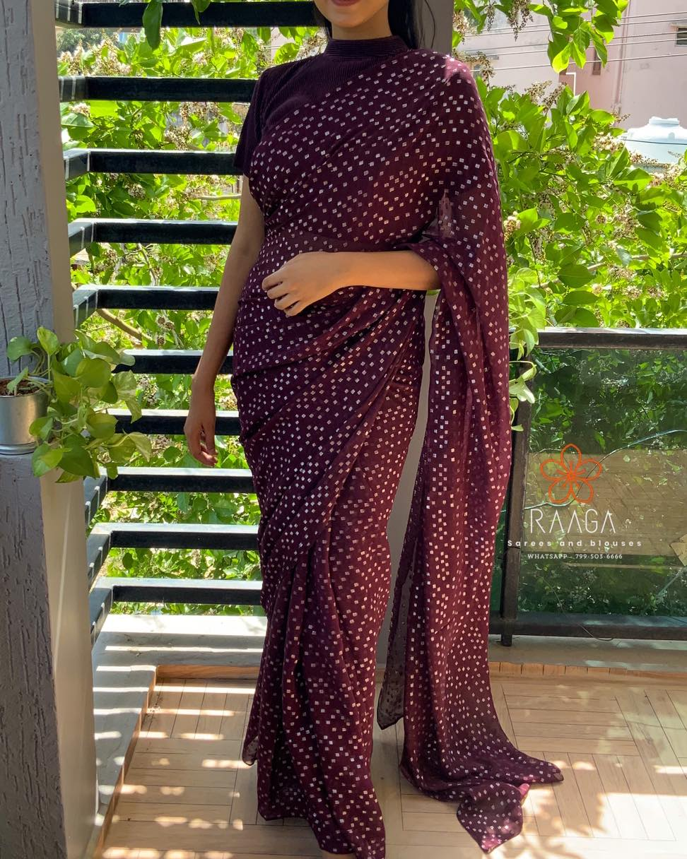 EASY BREEZY !  Style it your way !!  Soft chiffon saree in deep wine shade with silver dots all over the saree paired up with satin crushed high neck blouse .  . . Saree Only  - 3200 INR  Blouse material (unstitched ) - 650 INR  Handworked Waist belt (adjustable) - 2200 INR  Blouse stitching can be done at additional cost .  . . Kindly WhatsApp us at 7995036666 for placing orders . 2021-04-04