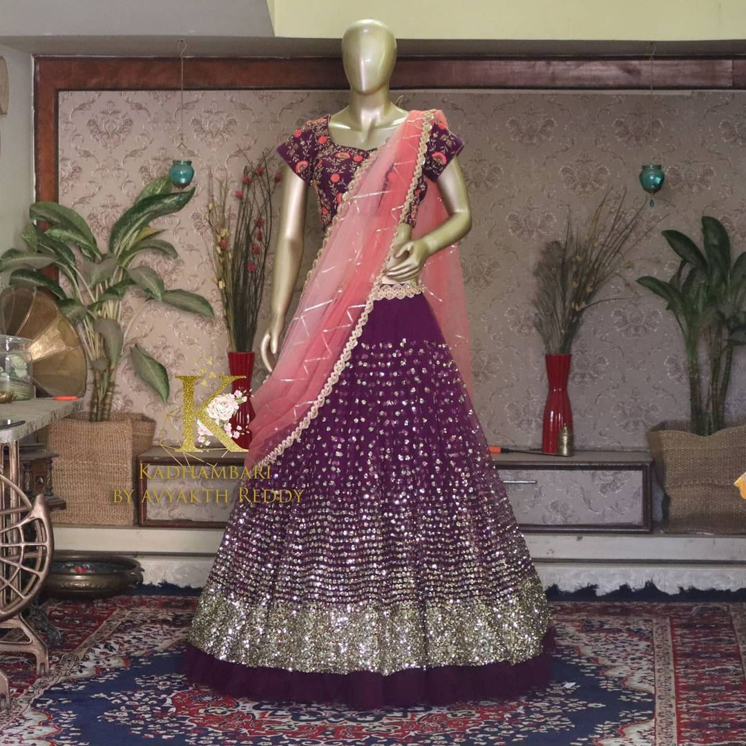 Gorgeous purple color net lehenga and blouse with net dupatta. Lehenga with mirror work. Blouse with floral hand embroidery work.  This outfit is Available at Rs 13800/- from house of Kadhambari. They can customize size as per your requirement. They have international shipping service too. For Orders and Enquiry Reach  on WhatsApp +91 8801876477 // +91 9063479099 2021-04-04