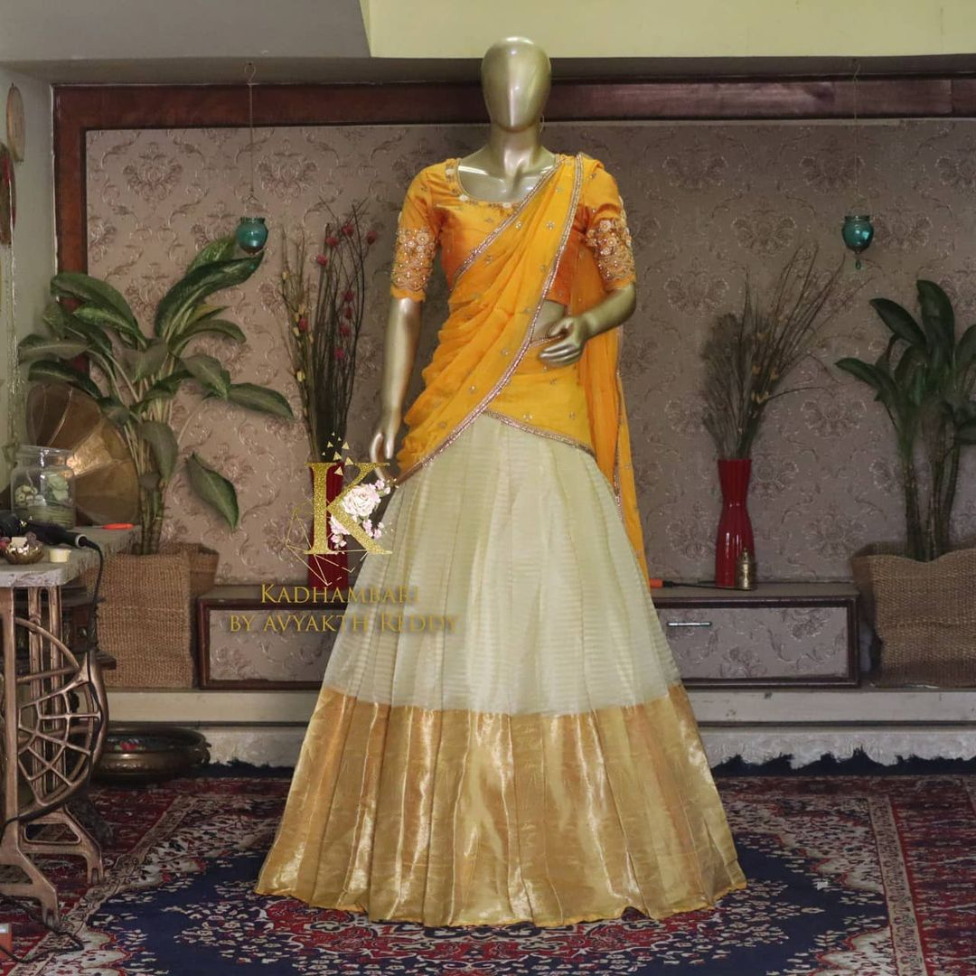 Stunning off white kanchi pattu lehenga and mustard yellow blouse with net dupatta. Blouse with hand embroidery work.  This outfit is Available at Rs 11800/- from house of Kadhambari. They can customize size as per your requirement. They have international shipping service too. For Orders and Enquiry Reach  on WhatsApp +91 8801876477 // +91 9063479099 2021-04-06