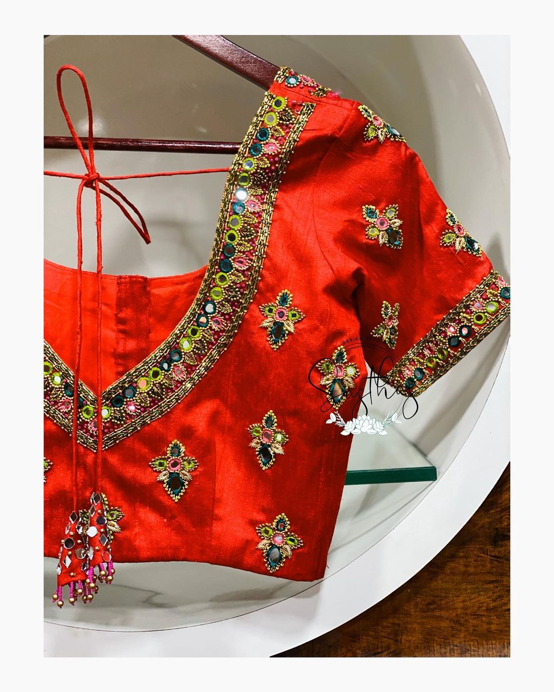 Gorgeous red color bridal blouse with V neck line and floral design hand embroidery mirror and bead aari work.  2021-04-20
