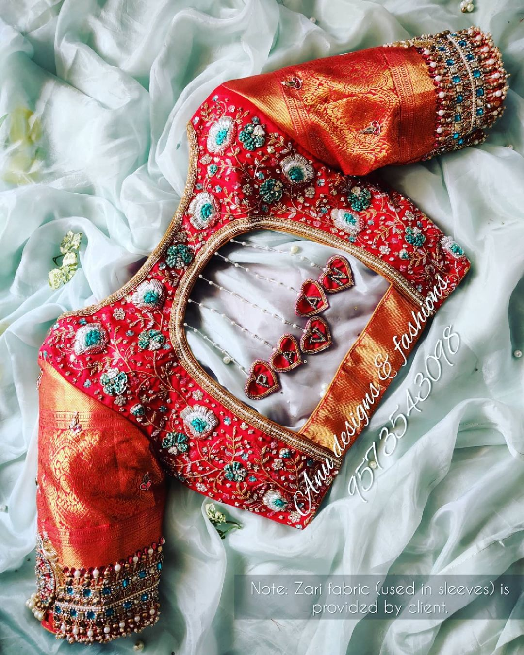 Gorgeous red color bridal blouse with creeper and floral design hand embroidery stone and bead maggam work. Blouse with groom name letters tassel hangings..   2021-04-25
