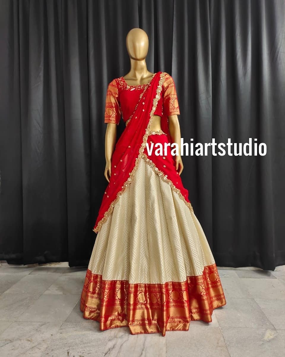Stunning off white and red color combination pattu lehenga and blouse with net dupatta. Blouse with zari sleeves. Blouse with hand embroidery work. Traditional pattu halfsaree.  2021-04-25