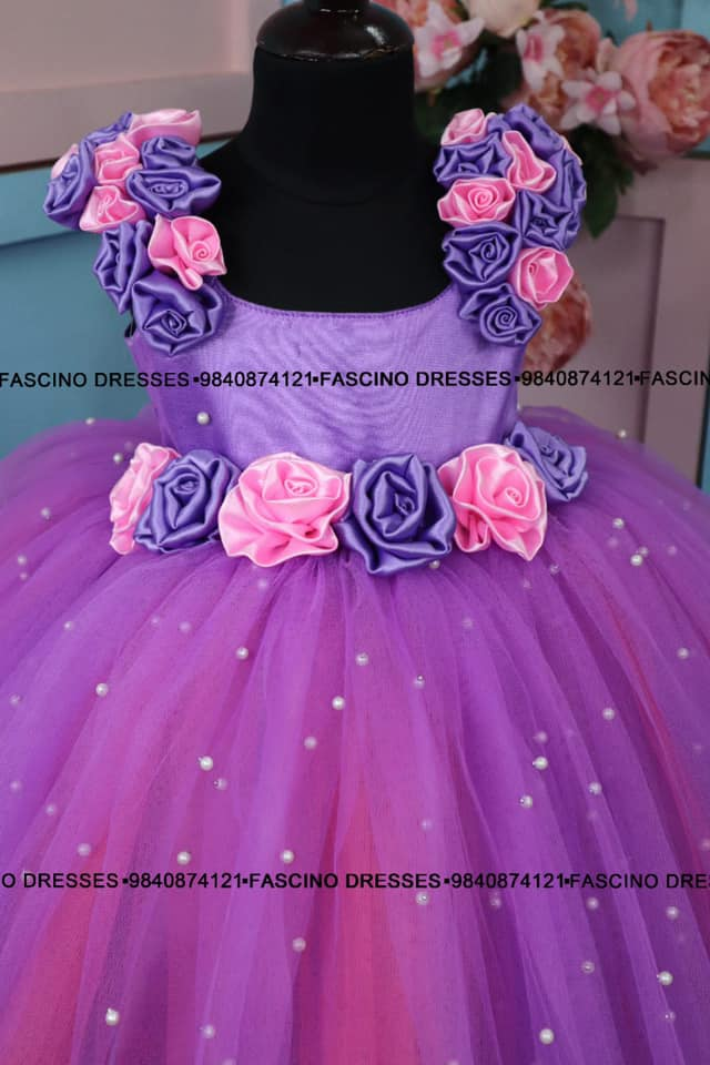 A lavander pink kids ballgown embellished with beautiful roses .