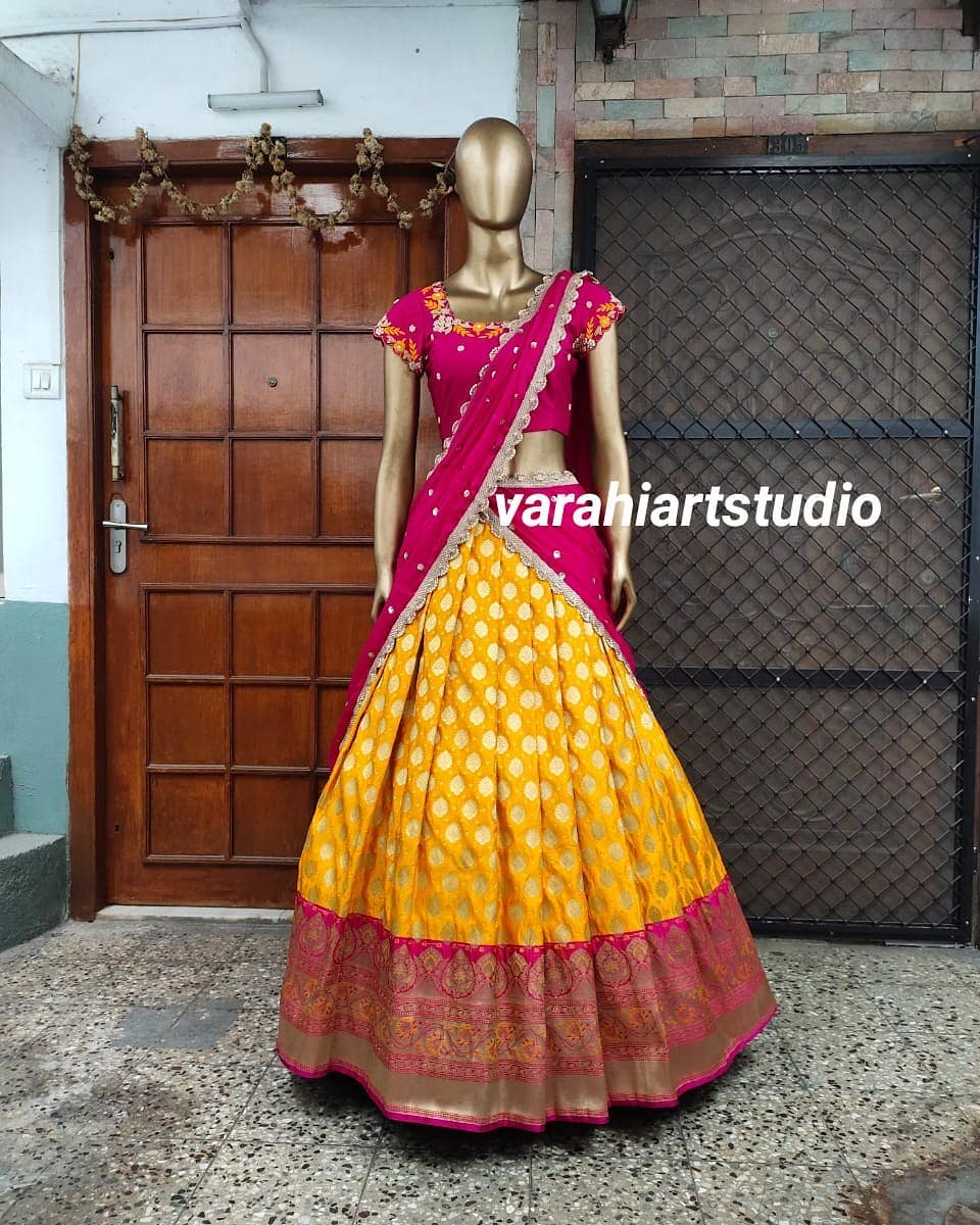 Stunning yellow colour pattu lehenga and pink blouse with net dupatta.  This outfit is Available Rs 10800 from Varahi art studio .. 2021-05-02