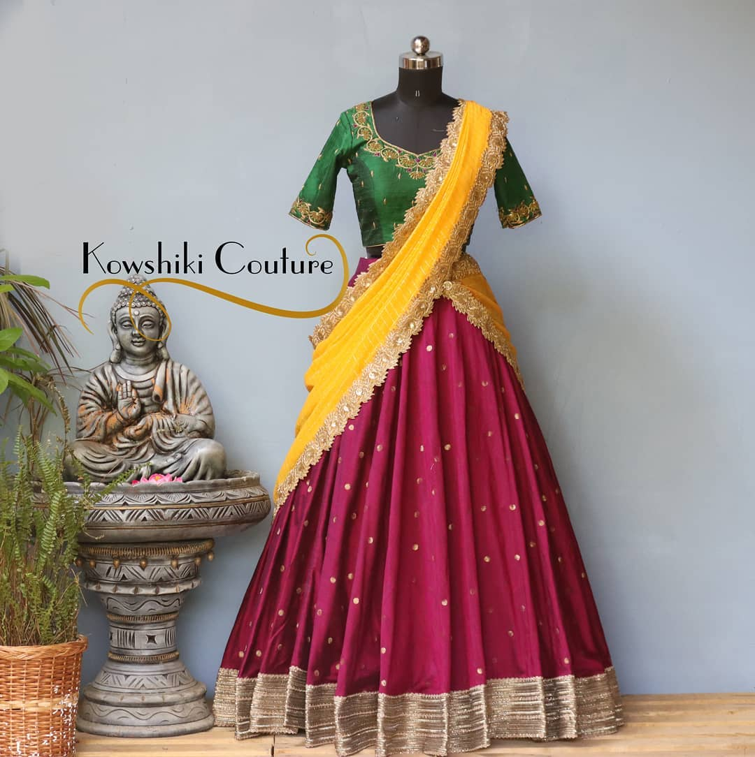 Maroon and Green pattu Half Saree paired with Yellow dupatta. Antique lace is attached all along the flared hem enhancing it's beauty. 2021-05-06