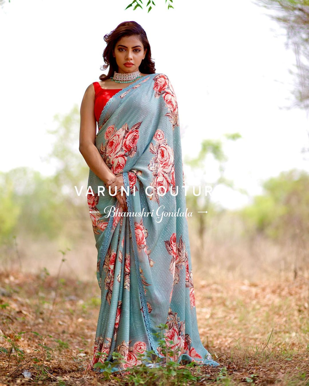 Stunning ice blue color floral saree and red color sleeveless blouse. Price 6999 INR