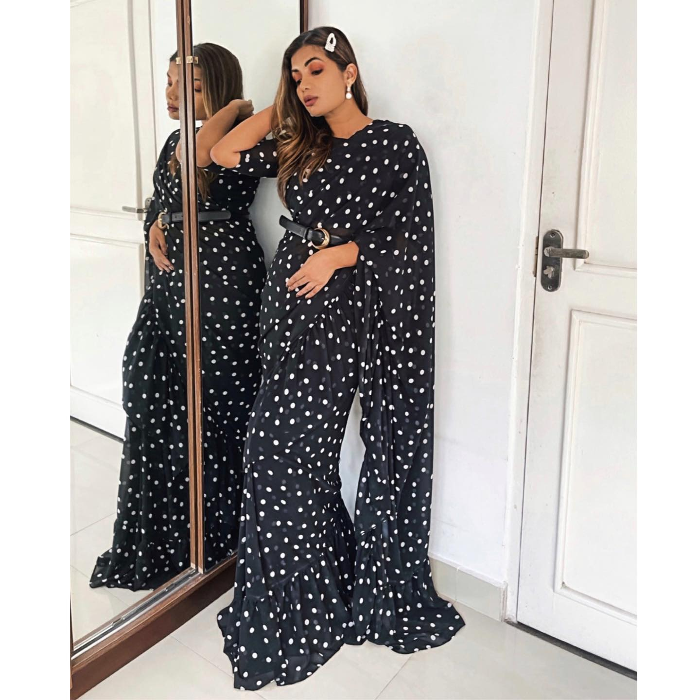 Beautiful monochrome polka ruffled sari in a creamy georgette. The blouse fabric is in the same fabric. Sari comes with a woven tassel fringe belt in black. 2021-05-11