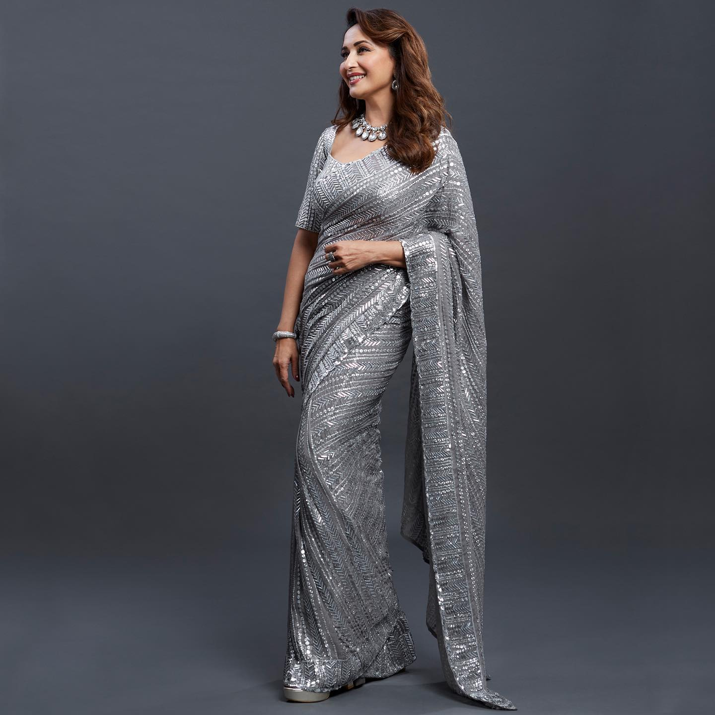The enchanting Madhuri Dixit Nene transcends a timeless aura in Manish Malhotra six yards of glamourous grey embroidered in signature Taban sequins. 2021-05-14