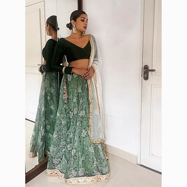 FORREST. This is a beautiful silk organza floral printed lehenga in deep green and ivory hues. The skirt is adorned with an ivory and gold sequin worked heavy border and hand made gold tassels to finish off the drawstring waist. The blouse is a deep green raw silk one with gold accents.  The dupatta is an off white soft net with a flat gold border.  2021-05-15
