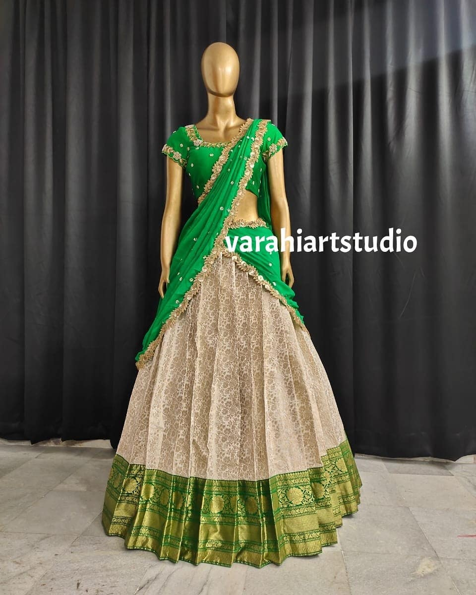 Stunning cream and green color combination traditional pattu langa voni. This outfit is Available Rs 11800 from Varahi art studio ..