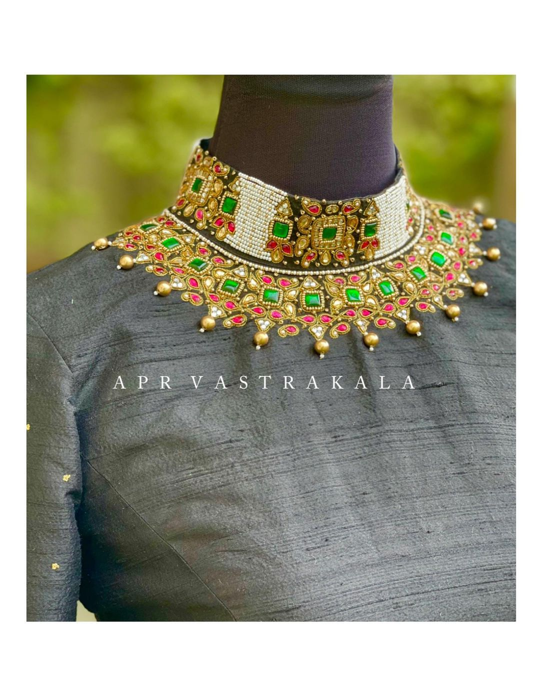 Design is a way of thinking...!! Gorgeous black raw silk high neck blouse with choker design hand embroidery emerald work on neckline and sleeves.  Designer Necklace work- Pearls n emeralds Apr vastrakala.  2021-05-16