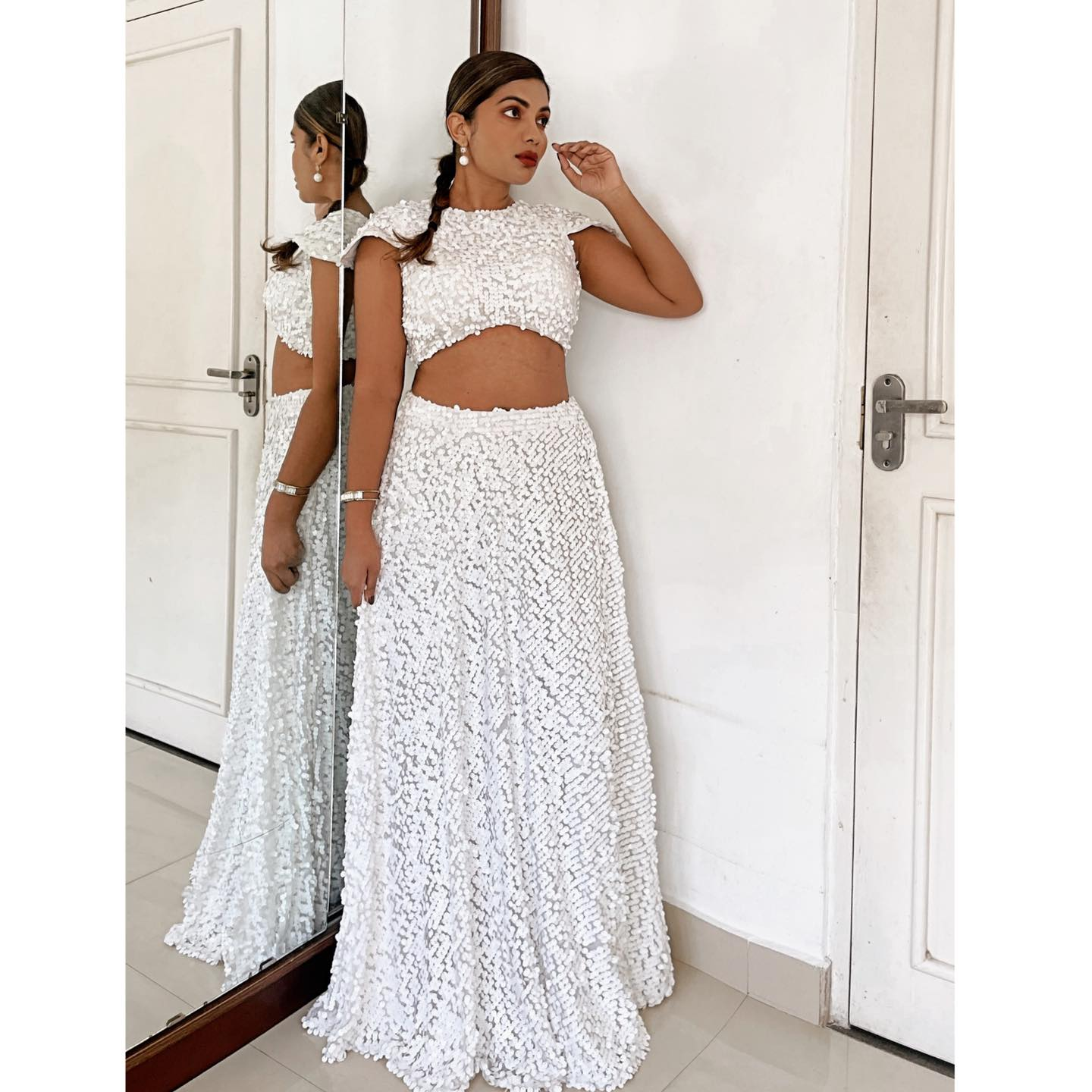 Full white matte sequin lehenga in S/M sizing. 34 inch bust and 30 inch waist.   STRICTLY ONE ONLY and no repeats.   Blouse is a beautiful cap sleeve design and the skirt has a fitted waist band. Blouse is fully padded.  2021-05-18