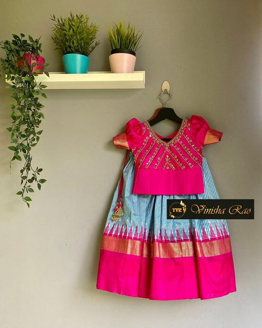 Ikat pattu baby lehenga comprises of Blue checks pleated lehenga teamed up with pink hand embroidered butta sleeves blouse for girls from the house of Vinisha rao designer studio !! Suitable for all kind of occasions !! .. . You can call us to order on