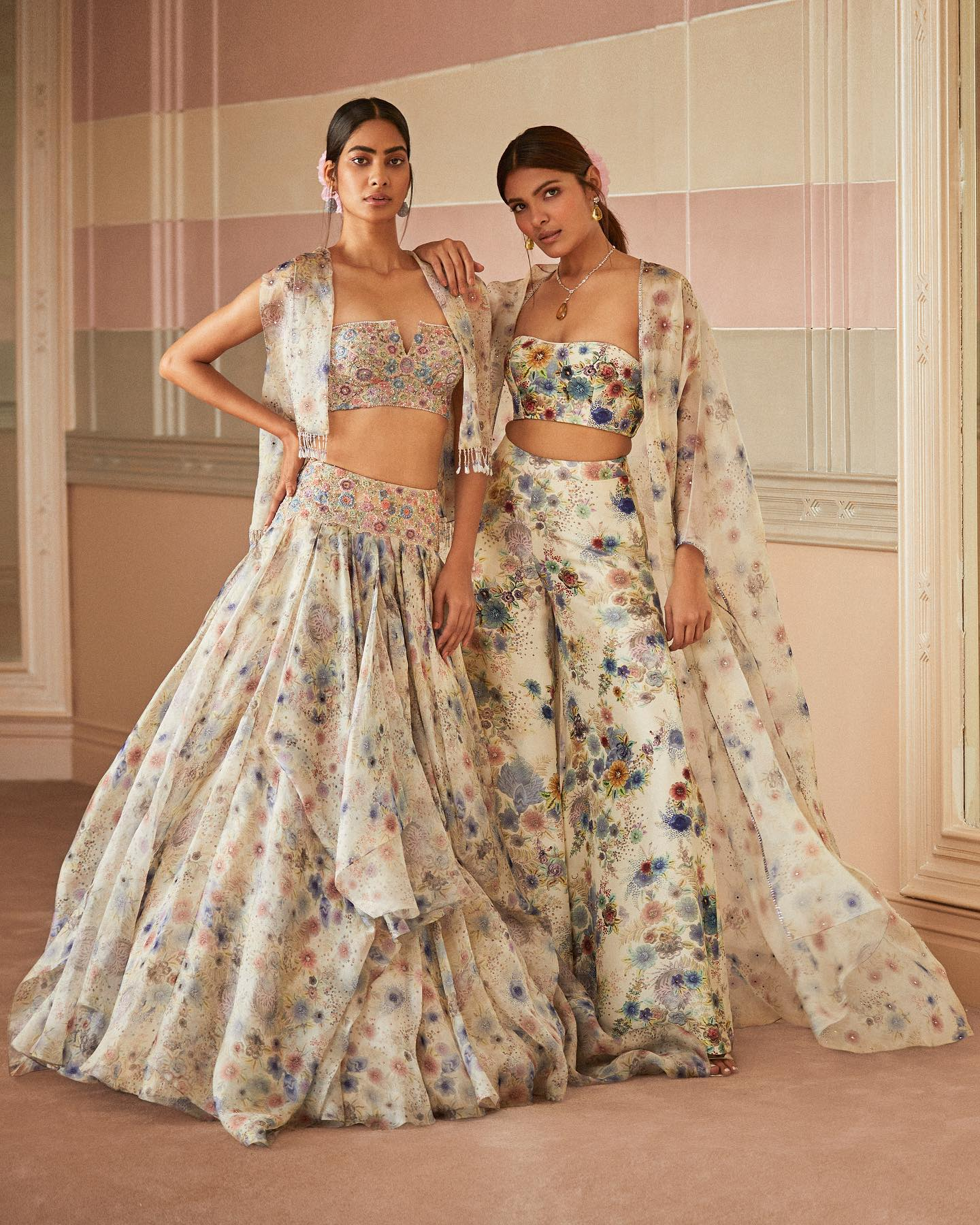 A vision in florals . Sumita is wearing a multi coloured voluminous lehenga with an embroidered hip yoke and bustier highlighted in resham and badla paired with a satin organza embroidered cape embellished with crystals.  Seen here on Richa is a set of dupion silk bustier and wide leg palazzos in shades of pastel. Paired with it is a sheer silk long cape highlighted with crystals. 2021-05-28