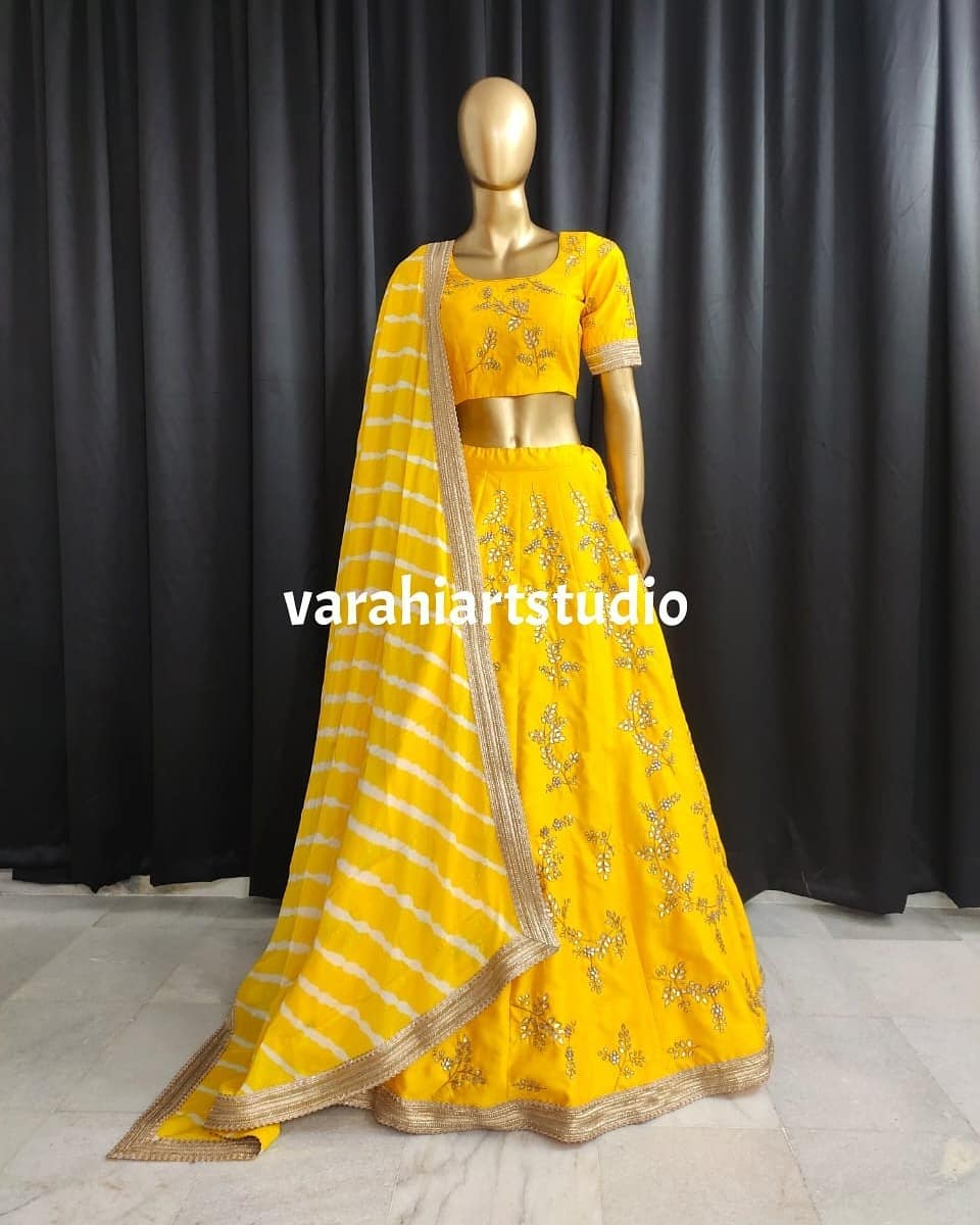 Lovely yellow color hand crafted bridal lehenga and blouse with leheriya dupatta. 2021-06-01