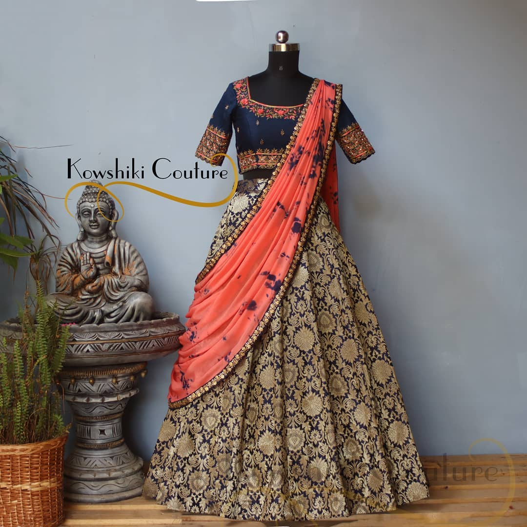 Royal blue Banarasi lehenga paired up with Peach duppatta and Royal blue blouse. Blouse adorned with intricate work in Peach & gold colour. The gold thread work on the blue lehenga is perfect to add a pop of colour to your wedding festivities! 2021-06-02
