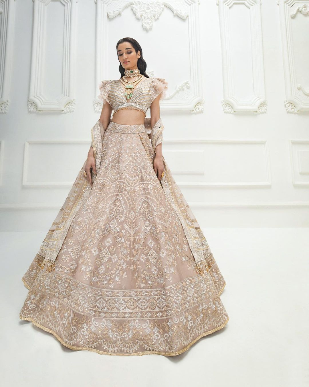 Adorn yourself in Rose honey celestial volumes divine pleated winged bodice extravagant ornaments like vintage zari textured sequins and metallic beads on floral #Tabān threadwork. 2021-06-03